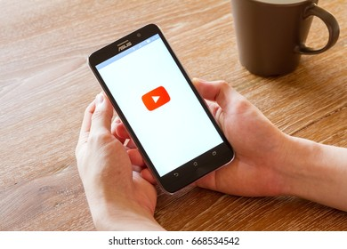 CHIANG MAI, THAILAND - APR 26, 2016: man hand holding screen shot of Youtube application showing on Asus Zenfone 2 mobile phone. YouTube is the popular video sharing website.