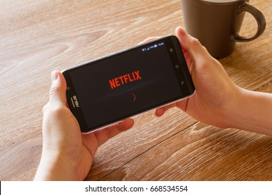 CHIANG MAI, THAILAND - APR 26, 2016: man hand holding screen shot of Netflix application showing on Asus Zenfone 2 mobile phone. Netflix is a global provider of streaming movies and TV series.
