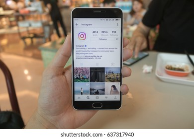 CHIANG MAI, THAILAND - APR 30,2017: Man holding Smartphone and using Instagram application on the screen.Instagram is largest and most popular photograph social networking.