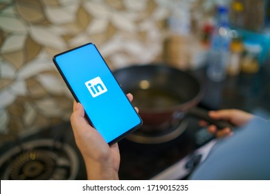 CHIANG MAI, THAILAND -Apr.5,2020: Woman holding Xiaomi Mi Mix 3 mobile phone with Linkedin application on the screen in the kitchen room at home.