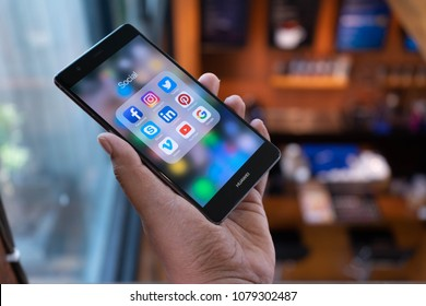 CHIANG MAI, THAILAND - April 21,2018: Man holding HUAWEI with icons of social media on the screen. Social media are most popular tool. Smartphone lifestyle. Starting social media app.