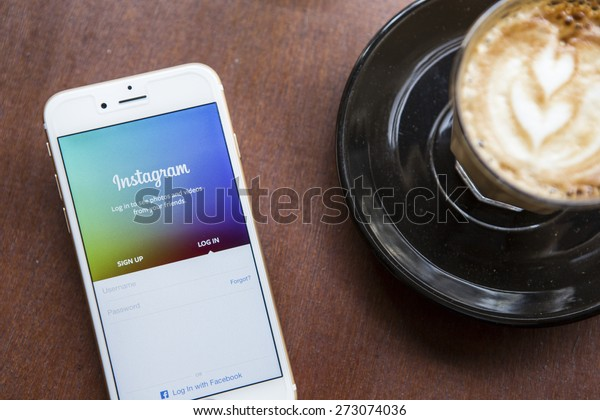 CHIANG MAI, THAILAND - APRIL 22, 2015: Instagram application using Apple iPhone 6 on coffee shop table. Instagram is largest and most popular photograph social networking site in the world.