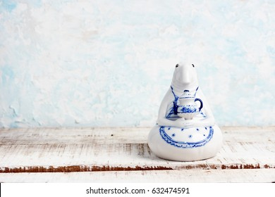 CHIANG MAI, THAILAND -?? April 28, 2017: Gzhel figure of Homunculus loxodontus with tea pot on wooden table, small copy of  Margriet van Breevoort sculpture