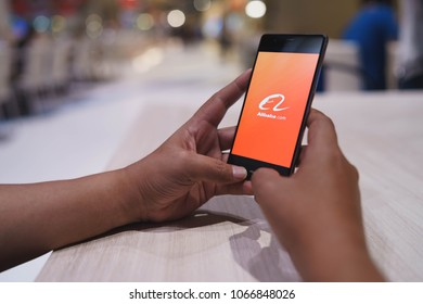 CHIANG MAI, THAILAND - April 4,2018: Man hands holding HUAWEI with alibaba apps on the screen. Alibaba's the the world's biggest online commerce company. Its three main sites Taobao,Tmall and Alibaba.