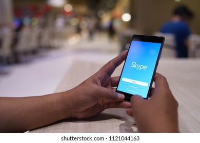 CHIANG MAI, THAILAND - April 4,2018: Man holding HUAWEI with skype apps at restaurant. Skype is part of Microsoft, can make video, audio calls, chat messages and do much more using Skype.