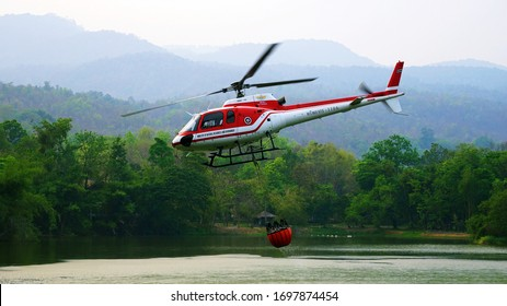 Chiang Mai, Thailand - April 8, 2020: Eurocopter AS350 of Ministry of Natural Resources and Environment collecting water in bucket from Ang Kaew Reservoir to douse forest fires on Doi Suthep mountain