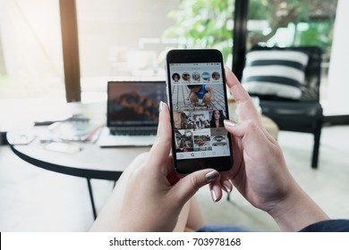 CHIANG MAI, THAILAND - AUG 14, 2017: A beautiful woman hand holding iphone with story and search page of instagram application. Instagram is largest and most popular photograph social networking.