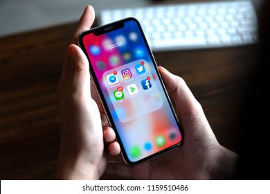 CHIANG MAI, THAILAND - AUG 18, 2018: Woman using iPhone X with icons of social media on screen, smartphone life style, smartphone era, smartphone in everyday life