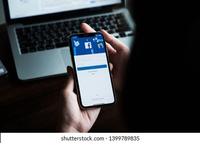 CHIANG MAI ,THAILAND - AUG 18, 2018 : Woman hand holding iPhone X to use facebook with new login screen.Facebook is a largest social network and most popular social networking site in the world.