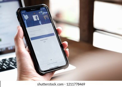 CHIANG MAI ,THAILAND - AUG 26, 2018 : Woman hand holding iPhone X to use facebook with new login screen.Facebook is a largest social network and most popular social networking site in the world.