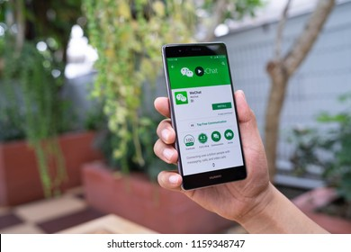 CHIANG MAI, THAILAND - August 05,2018: Man hands holding HUAWEI with WeChat  on the screen.WeChat is a Chinese multi-purpose messaging, social media and mobile payment app developed by Tencent.