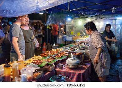 CHIANG MAI, THAILAND - AUGUST 27: Couple buys traditional Thai street food at the Saturday Night Market (Walking Street) on August 27, 2016 in Chiang Mai, Thailand.