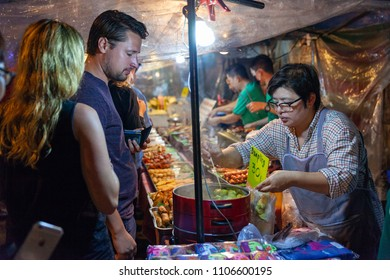 CHIANG MAI, THAILAND - AUGUST 27: Man buys dumplings at the Saturday Night Market (Walking Street) on August 27, 2016 in Chiang Mai, Thailand.