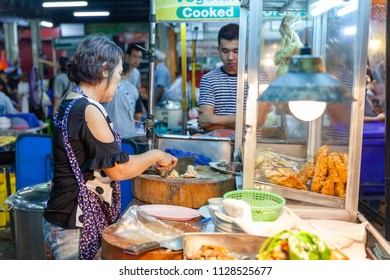 CHIANG MAI, THAILAND - AUGUST 27: Food vendor prepares chiken for sale at the Saturday Night Market (Walking Street) for sale on August 27, 2016 in Chiang Mai, Thailand.