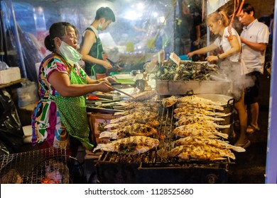 CHIANG MAI, THAILAND - AUGUST 27: Food vendor cooks fish at the Saturday Night Market (Walking Street) on August 27, 2016 in Chiang Mai, Thailand.