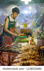CHIANG MAI, THAILAND - AUGUST 27: Food vendor prepares seafood at the Saturday Night Market (Walking Street) for sale on August 27, 2016 in Chiang Mai, Thailand.