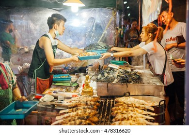 CHIANG MAI, THAILAND - AUGUST 27: Food vendor cooks and sells fish and seafood at the Saturday Night Market (Walking Street) on August 27, 2016 in Chiang Mai, Thailand.