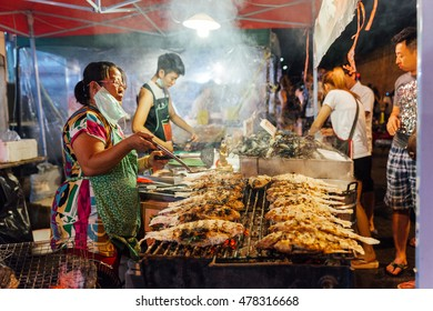 CHIANG MAI, THAILAND - AUGUST 27: Food vendor cooks fish and seafood at the Saturday Night Market (Walking Street) on August 27, 2016 in Chiang Mai, Thailand.