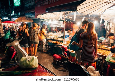 Chiang Mai, Thailand - August 27, 2016:  Tourists choose food at the Saturday Night Market on August 27, 2016 in Chiang Mai, Thailand.