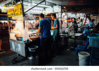 Chiang Mai, Thailand - August 27, 2016:  Father and sun cooking food at the Saturday Night Market on August 27, 2016 in Chiang Mai, Thailand.