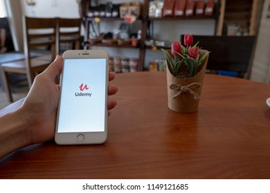Chiang Mai / Thailand - August 4 2018 :A man sit in cafe holding mobile with udemy screen