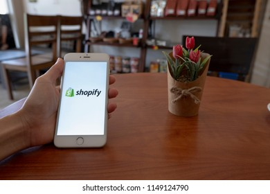 Chiang Mai / Thailand - August 4 2018 :A man sit in cafe holding mobile with shopify screen