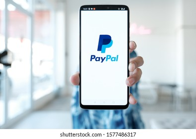 CHIANG MAI, THAILAND - Dec 1, 2019 : Woman hands holding Oneplus 6 with PayPal apps on the screen. PayPal is an online electronic payment system.