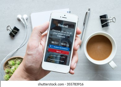 CHIANG MAI, THAILAND - DEC 20,2015:  A man holds Apple iPhone with Pinterest application on the screen. Pinterest is an online pinboard that allows people to pin their interesting things.