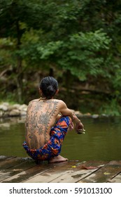 CHIANG MAI, THAILAND - DEC 4, 2013: Unidentified man with traditional thai sak yant tattoos squats near hot springs.