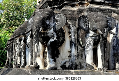 Chiang Mai, Thailand - December 19, 2012:   A row of carved elephants stands at the base of the Chedi at Wat Chiang Mun *