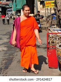 Chiang Mai, Thailand - December 23, 2012:  Young Buddhist monk wearing an orange robe walking to the Pung Tao Gong Chinese Ancestral Temple