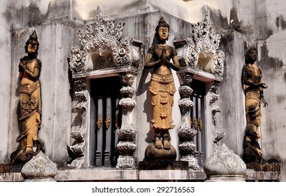 Chiang Mai, Thailand - December 25, 2012:  Statues of Thai Khong dancers decorate the base of an opulent white pagoda at Wat Nantaram  *