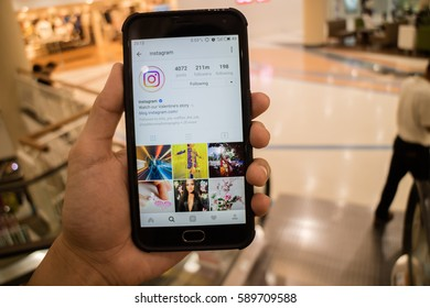 CHIANG MAI, THAILAND - FEB 14,2017: Man holding Smartphone and using Instagram application on the screen.Instagram is largest and most popular photograph social networking.