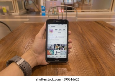 CHIANG MAI, THAILAND - FEB 18,2017: Man holding Smartphone and using Instagram application on the screen.Instagram is largest and most popular photograph social networking.