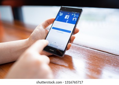 CHIANG MAI, THAILAND - FEB. 18,2019: Woman holding HUAWEI with facebook app on the screen. Facebook is a popular free social media are used for information sharing and networking.