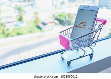 CHIANG MAI, THAILAND - Feb 22,2018: Apple iPhone 6S Rose Gold with Alibaba apps in a shopping cart. Online shopping via smartphone app concept.