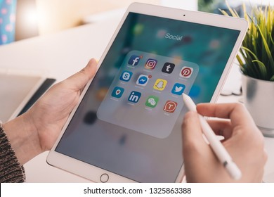 CHIANG MAI, THAILAND - FEB 24 , 2019: A woman holds Apple iPad Pro and apple pencil with icons of social media facebook, instagram, twitter, snapchat application on screen.
