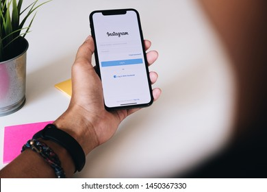 CHIANG MAI ,THAILAND - FEB 24 2019 : Man hands holding iPhone xs with Instagram application on the screen. Instagram is a popular online social networking service.