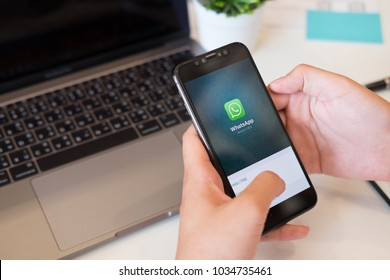 CHIANG MAI, THAILAND - FEB 28 2018 : Hands holding a iPhone X a new product apple open with social Internet service WhatsApp on the screen. iPhone X plus was created and developed by the Apple inc.