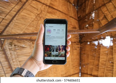 CHIANG MAI, THAILAND - FEB 8,2017: Man holding Smartphone and using Instagram application on the screen.Instagram is largest and most popular photograph social networking.