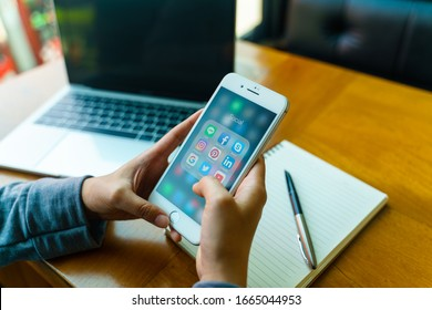 CHIANG MAI, THAILAND - Feb.23,2020: Woman holding Apple iPhone8 Plus with icons of social media on screen. Social media are most popular tool. Smartphone lifestyle. Starting social media app.