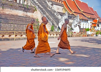 CHIANG MAI, THAILAND - FEBRUARY 05, 2015: The group of four buddhist monks dressed in traditional orange caps are cheerfully walking by the famous massive temple Wat Chedi Luang