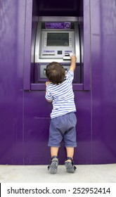 CHIANG MAI, THAILAND, FEBRUARY 10, 2015: A Little Boy Trying to Get Money at an SCB Bank ATM Machine. Siam Commercial Bank is the first bank of Thailand, informally established in 1904 as Book Club.