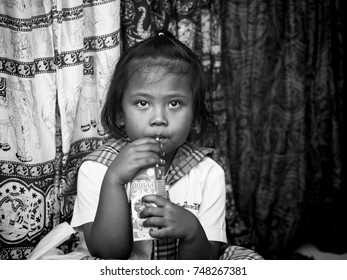 Chiang Mai, Thailand - February 24: Young unidentified girl drinks with straw on February 24, 2015 in Chiang Mai, Thailand.