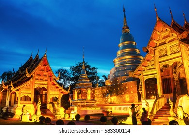 Chiang Mai, Thailand. Illuminated temples of Phra Singh in Chiang Mai, Thailand at sunset. Golden walls and blue sky