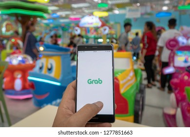 CHIANG MAI, THAILAND - JAN. 06,2019: Man holding HUAWEI with Grab apps on screen. Grab is smartphone app all-in-one transport booking in South-East Asia.