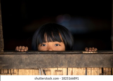 Chiang Mai / Thailand - Jan 16 2016 : An Asian girl hides in a wooden house and peeks out of the window, sees the top half of the face, handles on the windowsill, in rural northern Thailand.