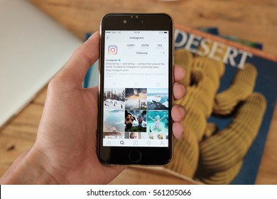 CHIANG MAI, THAILAND - JAN 16 ,2017: A man holds Apple iPhone with Instagram application on the screen. Instagram is a photo-sharing app for smartphones. with people meeting background