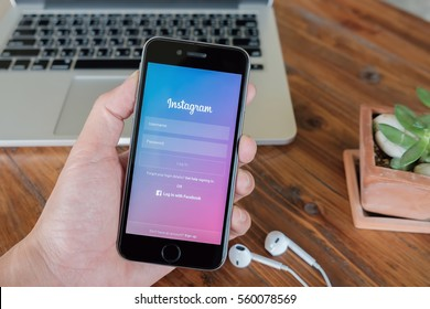 CHIANG MAI, THAILAND - JAN 18, 2017: A woman holds Apple iPhone 6S with Instagram application on the screen with latte hot, coffee cup on wood desk. Instagram is a photo-sharing app for smartphones.