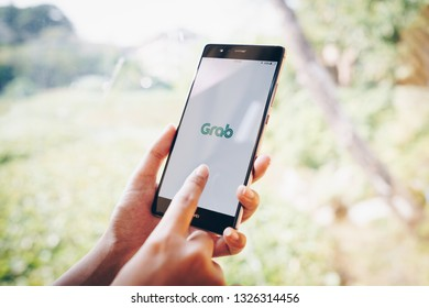 CHIANG MAI, THAILAND - JAN. 19,2019: Woman holding HUAWEI with Grab apps on screen. Grab is smartphone app all-in-one transport booking in South-East Asia.